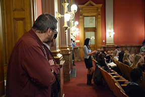 Rocky Mountain HS ournalism adviser Stephan Wahlfeldt and former journalism student Loren Collins listen in as student journalist Stephanie Llorente of Regis Jesuit as she asks a question of Rep. Millie Hammer.  Photo by Evan Malone