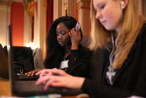 Conifer student journalist Audrey Dilgarde, left, listens to a voice recording on her phone while writing her news piece during the on-site competition at the end of the 2015 Capitol Hill Press Conference. Photo by Forrest Czarnecki