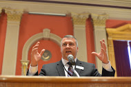 Colorado Education Commissioner Richard Crandall gets animated as he describes his son's new taser gun, which he somehow related to AP testing. Photo by Holly Knutsen